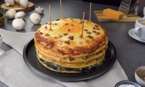 Refeição farta: torre de omeletes com vegetais, queijo e bacon